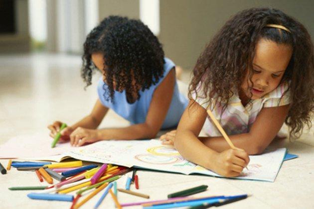 Meninas desenhando deitadas no chão