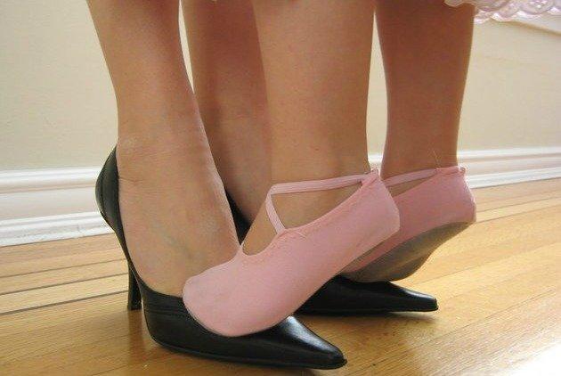 Menina de sapatilha dançando em cima dos pés da mãe