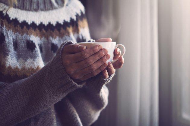 Pessoa agasalhada segurando xícara de chá