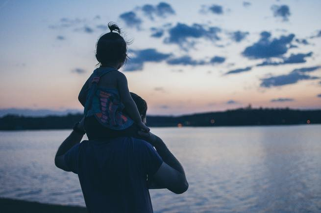 A daughter being carried on her father's shoulders.