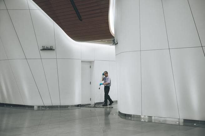A custodian cleaning the floor of a building.