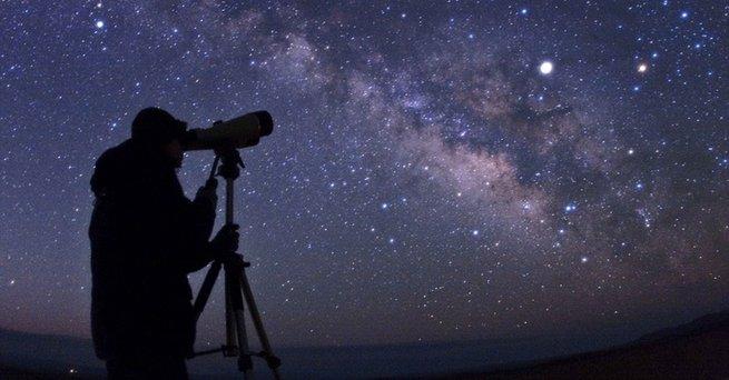 Pessoa observando céu estrelado com telescópio