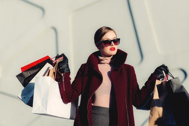 A woman holding several bags of luxury shopping.